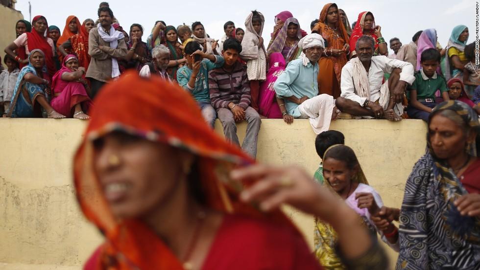 Men and women watch people taking part in huranga at Dauji temple on March 28.