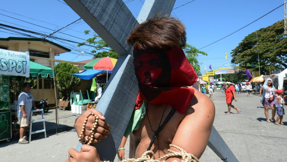 A portrait of Jesus covers a penitent's face as he carries a cross during a Holy Week ceremony in the northern province of Pampanga in the Philippines.
