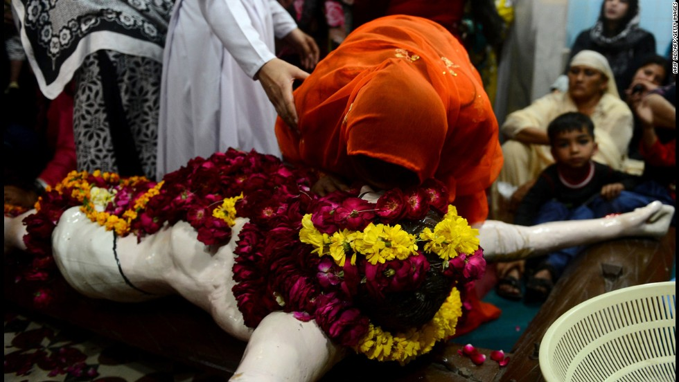 A Christian devotee touches a statue of Christ during a Good Friday service at Saint Francis Church in Lahore, Pakistan, on Friday.