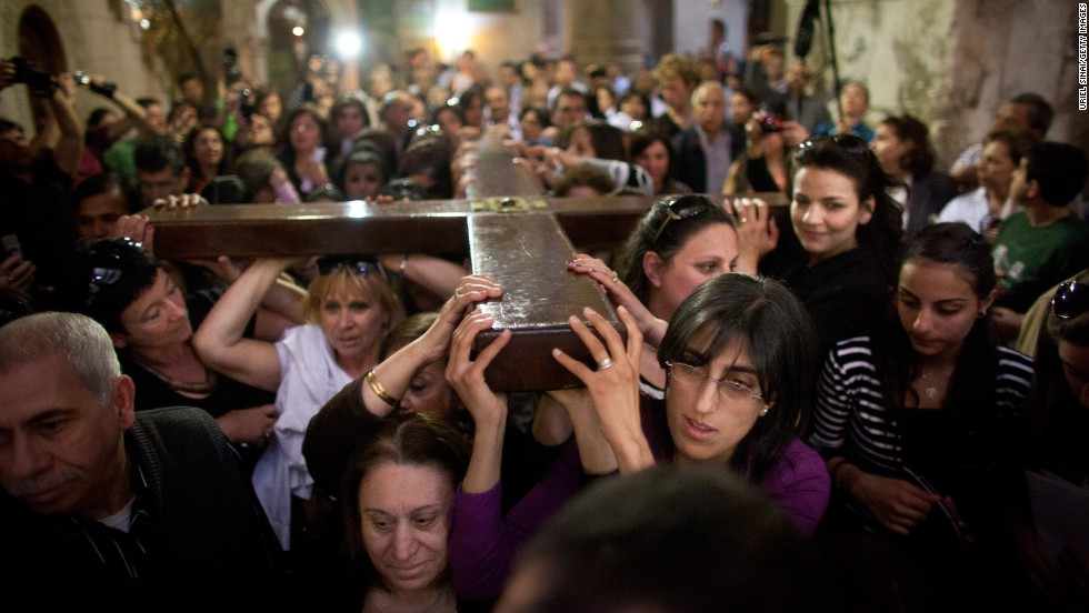 Christian worshippers carry a large wooden cross at the Church of the Holy Sepulchre during the Good Friday procession in Jerusalem's Old City.
