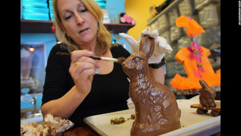 Darlene Eddy uses a brush to remove chocolate shavings from an Easter bunny in her store, Amazing Chocolates, on Thursday, March 28, in Hollywood, Florida.
