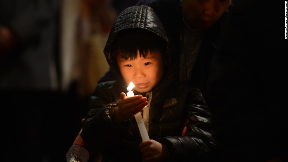 A child holds a candle during an Easter service at the Cathedral of the Immaculate Conception in Beijing on Saturday.