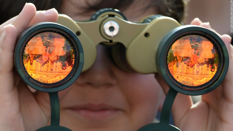 An attendee looks at St. Peter's Basilica through binoculars on Sunday.