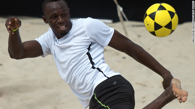 "Usain Bolt plays ""foovolley"" in a promotional event at Copacabana beach in Rio de Janeiro ahead of his 150m race."