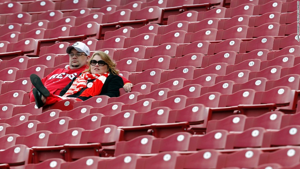 Cincinnati Reds fans watch their team practice before their game against the Los Angeles Angels of Anaheim in Cincinnati.