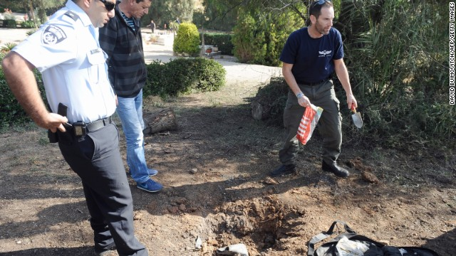 A bomb technician collects the remains of a rocket launched from Gaza Strip falling close to Sderot on April 3, 2013.