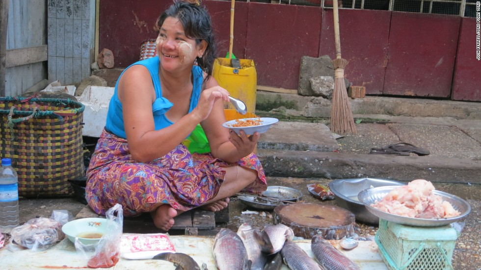 A fish vendor pauses to enjoy a meal in the middle of her workday.