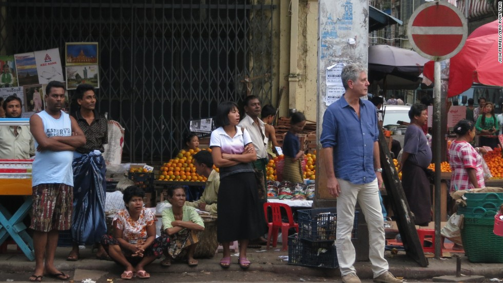 Anthony Bourdain waits for the bus during rush hour in Yangon.