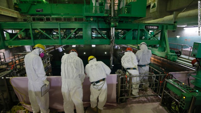 This file photo taken on March 6, 2013 shows workers wearing protective suits and masks next to the spent fuel pool inside the Common Pool Building.