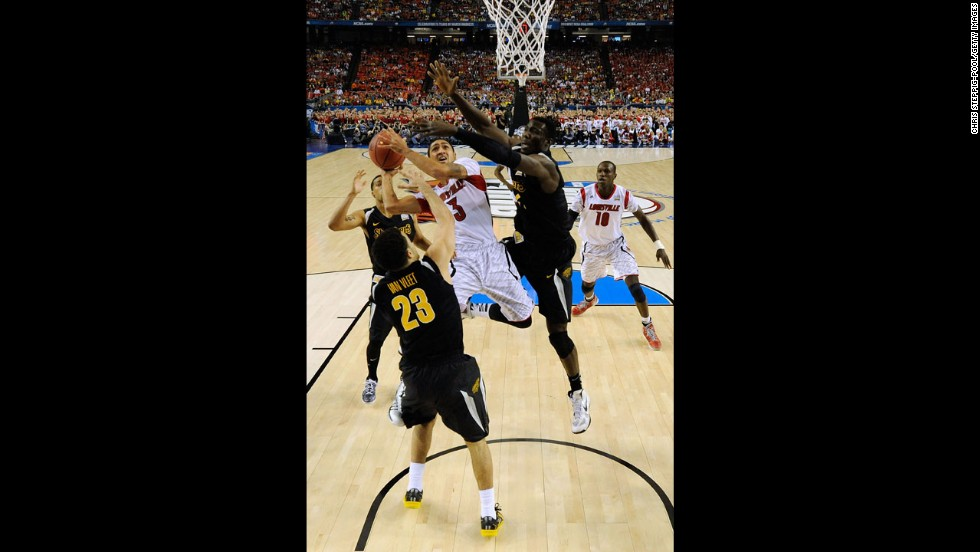 Peyton Siva of Louisville drives for a shot attempt against Fred VanVleet, left, of Wichita State.