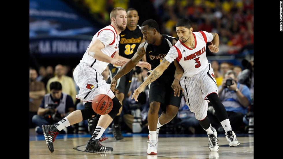 Malcolm Armstead of Wichita State, second right, attempts to control the ball against Stephan Van Treese, left, and Peyton Siva, right, of Louisville.