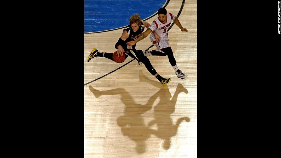 Ron Baker of Wichita State brings the ball up court against Peyton Siva of Louisville.