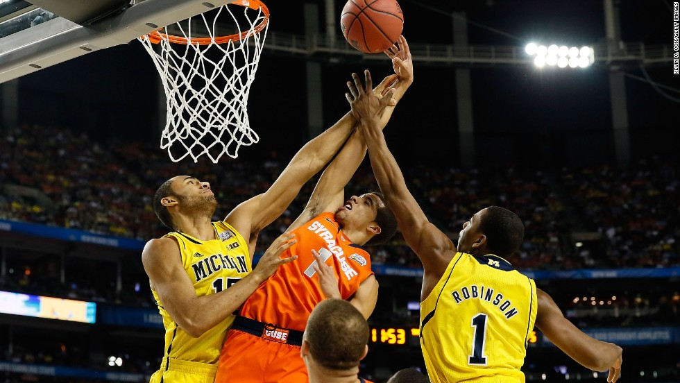 Michael Carter-Williams of the Syracuse Orange drives for a shot in the first half against Jon Horford, left, and Glenn Robinson III, right, of the Michigan Wolverines.