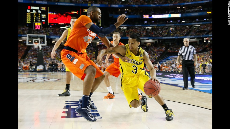 Trey Burke of Michigan drives in the second half against James Southerland of Syracuse.