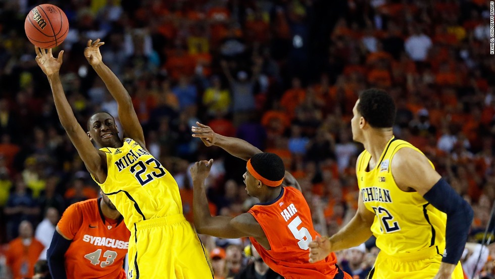 Caris LeVert of Michigan passes the ball to teammate Jordan Morgan in the final seconds before Morgan dunks it.