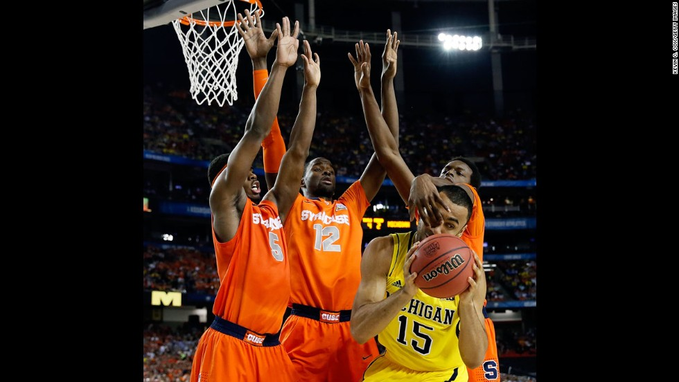 Jon Horford of Michigan attempts to pass the ball as he is defended by, left to right, C.J. Fair, Baye Moussa Keita and Jerami Grant of Syracuse.