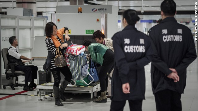 Customs officers monitor baggage checking at a border crossing point with mainland China in Hong Kong on March 1, 2013.