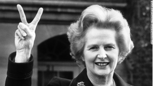 November 1976: Conservative party leader Margaret Thatcher makes a 'victory' sign outside her home in Chelsea, London.