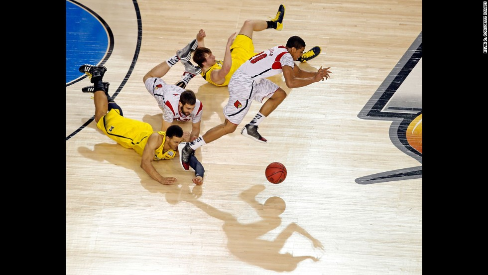 Wayne Blackshear of Louisville, right, and Jordan Morgan, bottom left, of Michigan go after a loose ball.