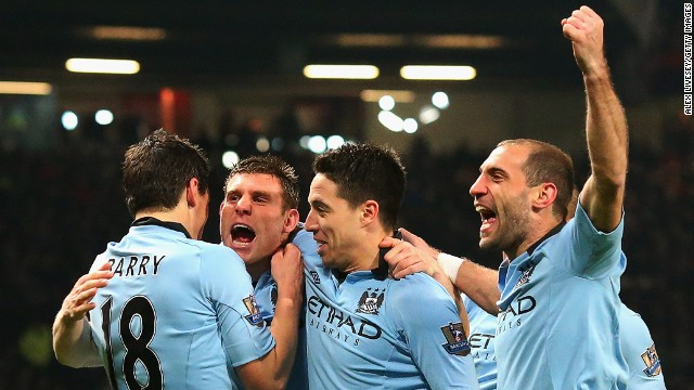 Manchester City players celebrate the opening goal by James Milner (second from left) as they stunned United at Old Trafford