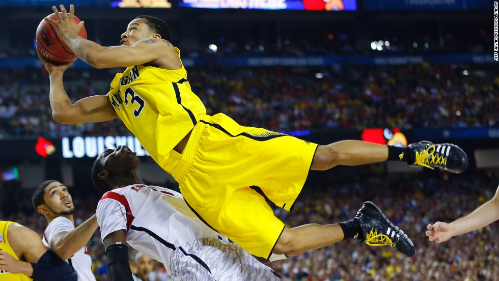 Trey Burke of Michigan drives to the hoop against Gorgui Dieng of Louisville.
