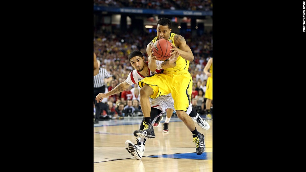 Trey Burke of Michigan attempts to control the ball against Peyton Siva of Louisville.