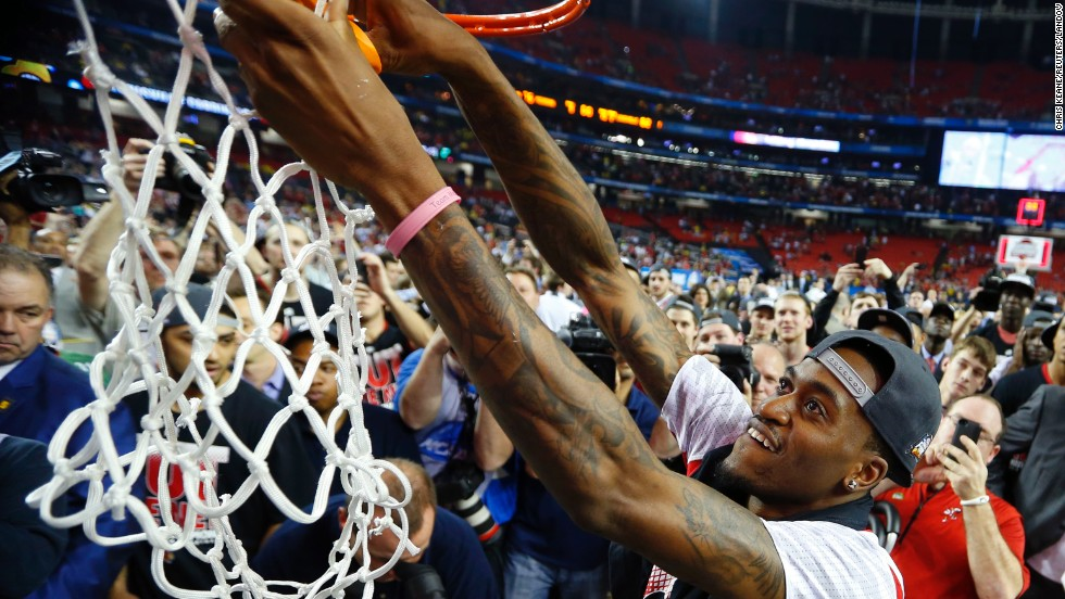 Injured Kevin Ware of Louisville cuts down the net, which was lowered to the court floor for him.