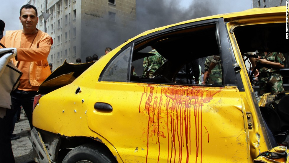 Rescue teams and security forces check out the scene of a deadly car bomb explosion in Damascus on April 8.