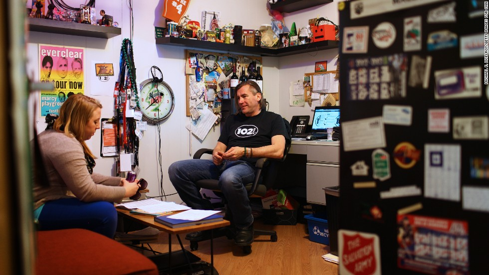 Randy Malloy, CD102.5's president and general manager, chats with marketing director Kara Jones in his office. The station, which isn't part of a larger media corporation, has been independently owned and operated for more than two decades.
