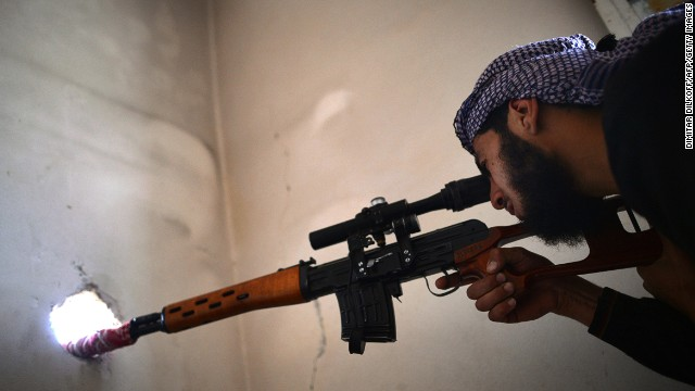 A Syrian rebel sniper observes the movement of Syrian government forces near Al-Kendi hospital in Aleppo on Wednesday.