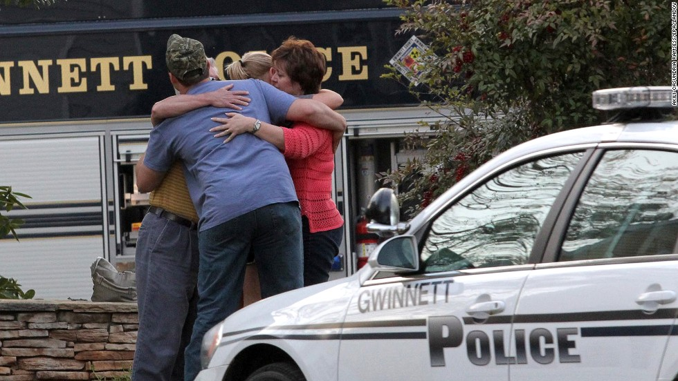 Neighbors embrace after a hostage situation ends in Suwanee, Georgia, on Wednesday, April 10. A gunman in apparent financial distress took several firefighters hostage the Atlanta suburb, then was killed in an exchange of gunfire hours later after law enforcement authorities determined he might lash out at his captives.