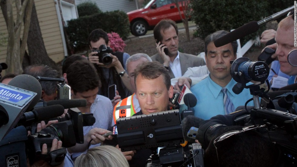 """Gwinnett County police spokesman Ed Ritter, center, addresses the media Wednesday night. """"It got to the point where we believed that (the firefighters') lives were in immediate danger,"""" he said. """"And our SWAT team made the decision to go in there and neutralize the situation."""""""