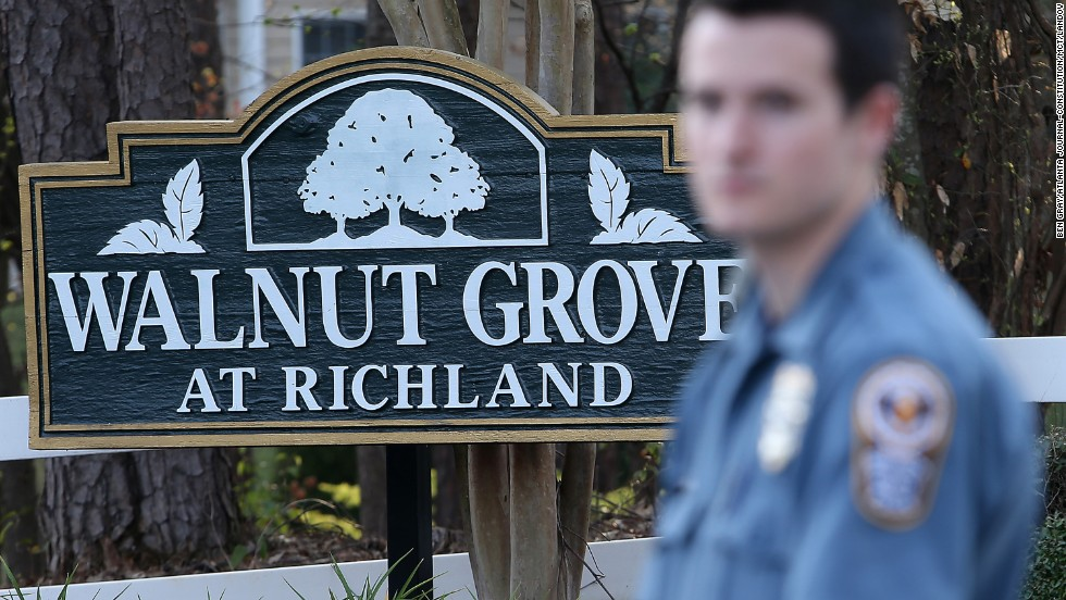 A police officer stands guard in the Walnut Grove subdivision in Suwanee, where the incident took place.