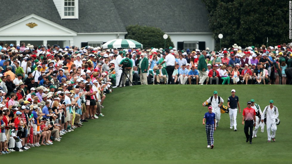 Left to right: Ian Poulter of England, Steven Fox and Bubba Watson of the U.S. walk up the fairway on the first hole.