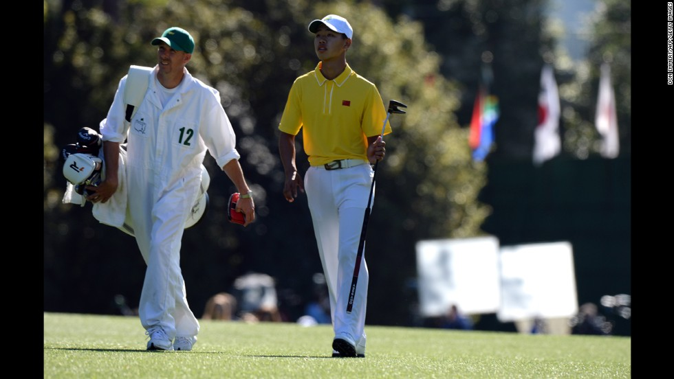 Guan Tianlang of China walks with his caddie during the third round.