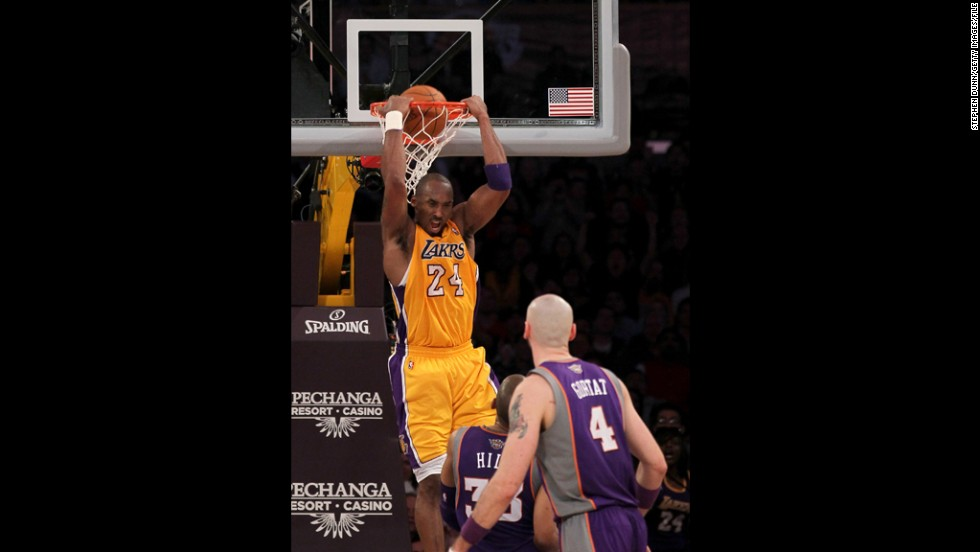Bryant reverse dunks over Grant Hill, No. 33, and Marcin Gortat, No. 4, of the Phoenix Suns at Staples Center on January 10, 2012, in Los Angeles. The Lakers won 99-83.