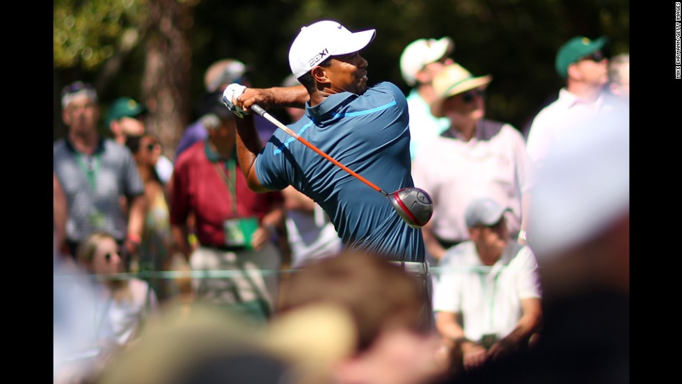 Tiger Woods hits a tee shot on the ninth hole.