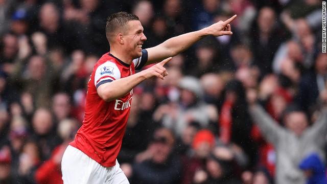 Lukas Podolski celebrates scoring Arsenal's third goal in the 3-1 over Norwich at the Emirates Stadium.
