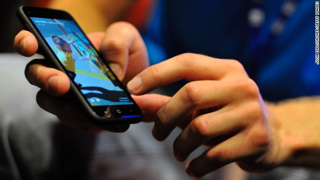 A Facebook employee displays an HTC phone with the new Home operating system.