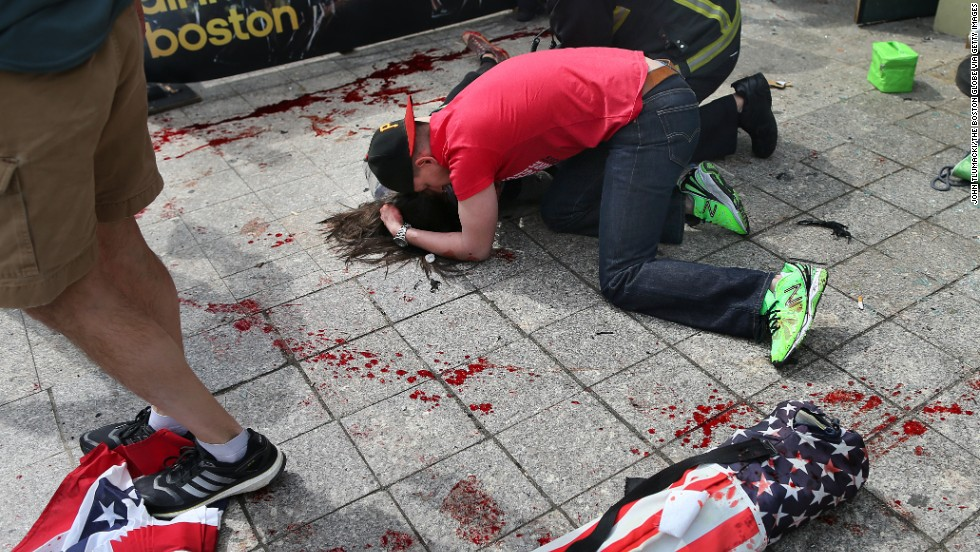 A man comforts a victim on the sidewalk at the scene of the first explosion.