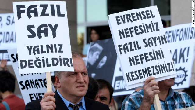 "A poster reads ""Fazil Say is not alone,"" left, at a protest outside an Istanbul court on October 18, 2012."