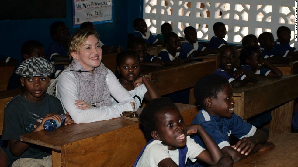 Madonna sinks flanked by the two Malawian children she adopted -- David Banda and Mercy James -- in a classroom at Mkoko Primary School, central Malawi, on April 2, 2013.