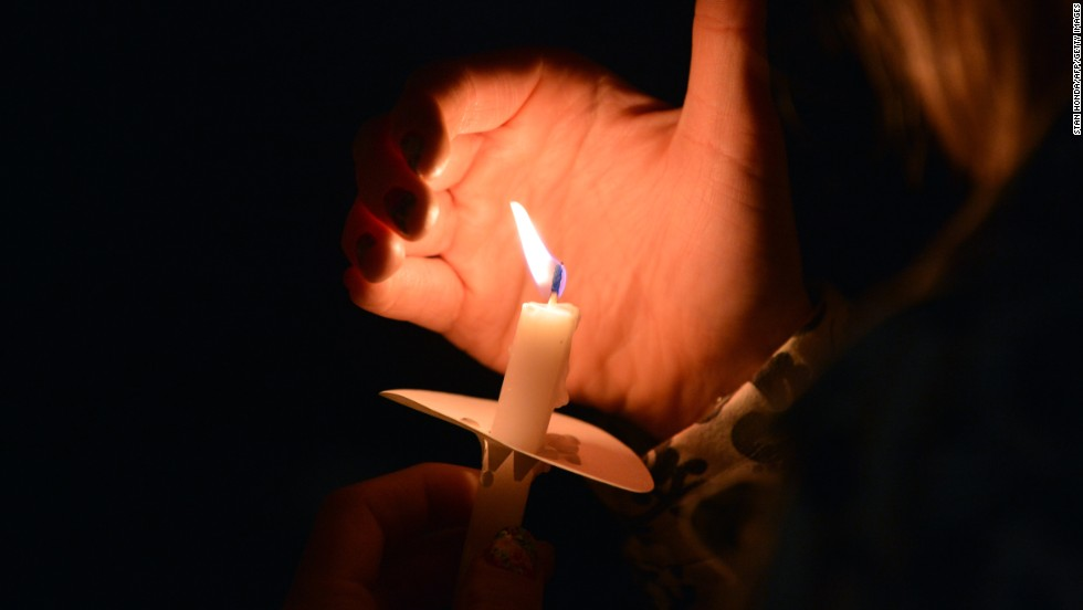 A woman uses her hand to keep wind from her candle during an interfaith service in Boston on April 16, 2013.