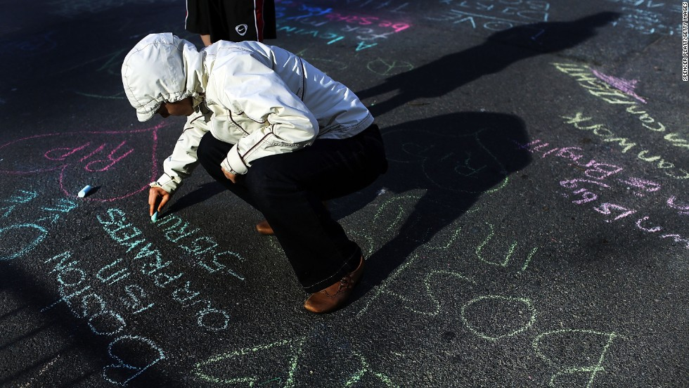 Danielle Cerroni writes a chalk message on the street near the marathon's finish line on April 17, 2013.