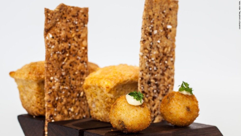 Guests at Dovetail's bar are served a complimentary snack trio consisting of a truffle arancini, a whole wheat rosemary cracker and house-made white cheddar cornbread. Dainty and delicious, it's served on a wooden cheese board.