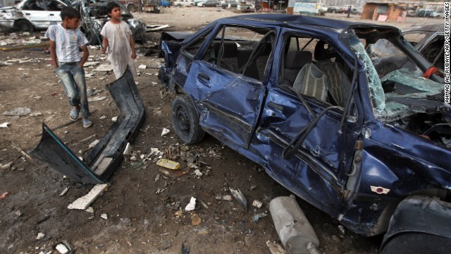 Iraqi boys inspect the site of a car bomb attack in Baghdad's district of Sadr City on April 16, 2013.