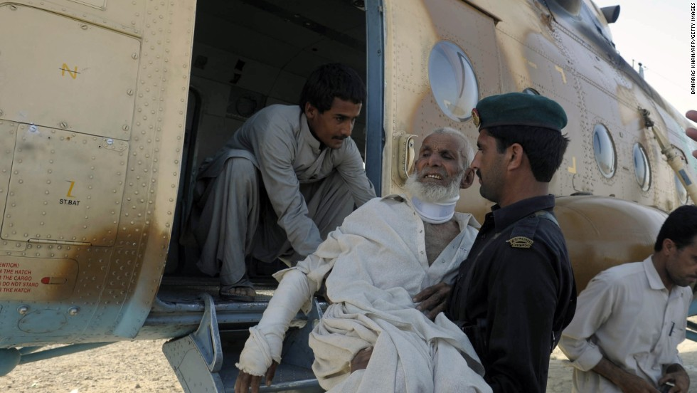 A Pakistani Frontier Constable carries an injured earthquake survivor into an army helicopter in Mashkell on Thursday.