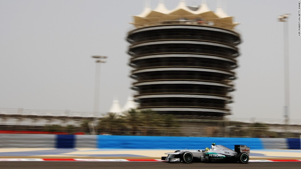 The imposing Sakhir Tower looms over the cars as they race on the Bahrain International Circuit.