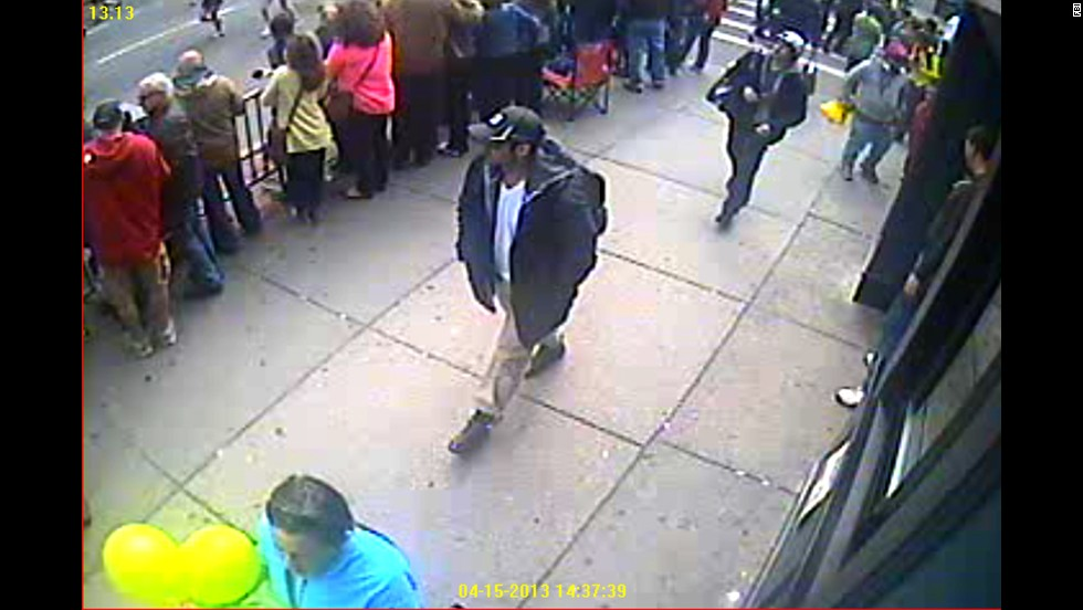 Both suspects are seen walking through the crowd.
