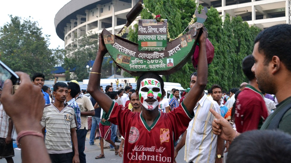 Outside of Saltlake Stadium, a fan wears the Mohun Bagan A.C. shirt and celebrates the last match of Brazilian player Jose Ramirez Barreto. Thousands of Barreto fans arrived to express their adoration, despite the fact that the revered footballer was simply switching teams and not leaving the game altogether.